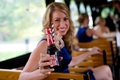 Bridesmaid in a sleeveless sapphire blue dress holds mini bottle of Chandon Rosé
