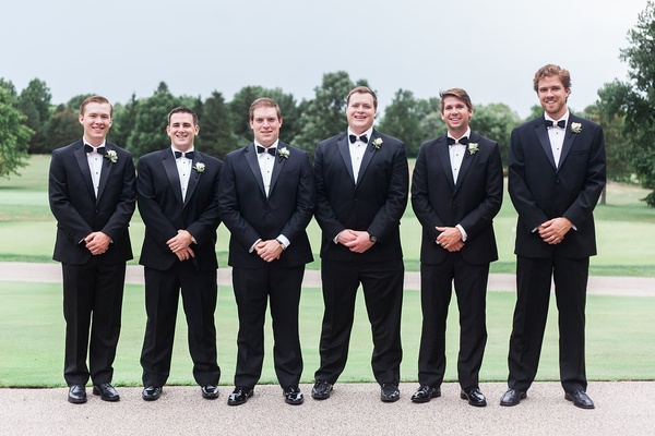 Groomsmen in front of golf course with tuxedos on and bow ties from collared greens