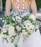 Back of Angel Sanchez wedding dress buttons flower applique vines and loose bouquet greenery