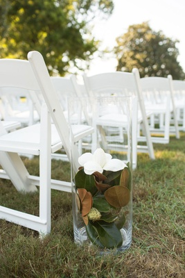 Wedding ceremony white chairs with hurricane vase filled with magnolia flower and magnolia leaves
