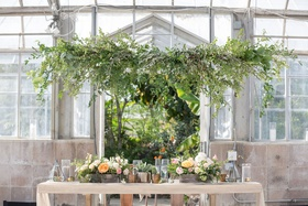 greenhouse wedding venue reclaimed wood sweetheart table greenery overhead low centerpiece rustic