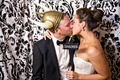 "Bride kisses groom with ""Censored"" sign in damask print photobooth"