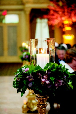 Wedding ceremony with candles in glass hurricanes surrounded by purple orchids and greenery