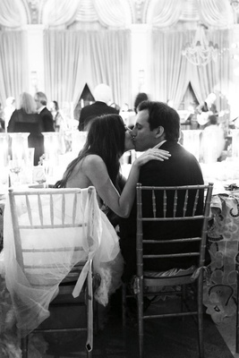 Black and white photo of couple kissing at wedding reception