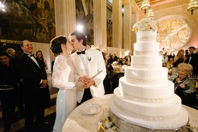 wedding reception cake cutting new year's eve bride in long sleeve illusion lace dress kissing groom