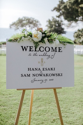 wedding welcome sign fern tropical leaves flowers pineapple monogram on wood easel outdoor ceremony