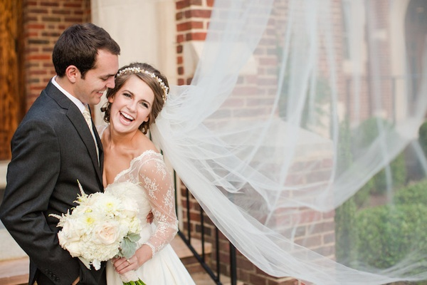 Bride and groom smile in front of brick building