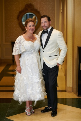 bride in feathered stephen yearick reception dress, groom in white tuxedo jacket