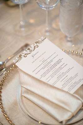 Menu card on top of silky napkin and gilt-rimmed charger