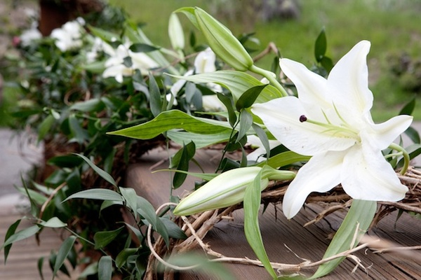 White lilies, greenery, and branch outdoor decorations