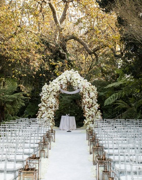 Hotel Bel-Air wedding ceremony outdoor white flower arch with gold lanterns clear chairs white aisle