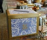 Wedding reception with a golden box with blue and white decoration and couple's monogram