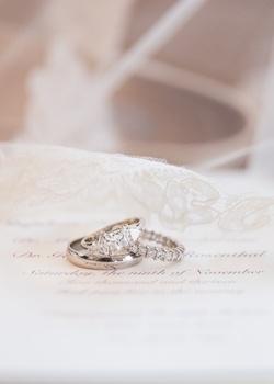 Three-stone diamond engagement ring, princess cut diamond wedding band, and groom's wedding band