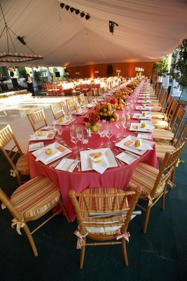 White tented wedding reception with colorful tables