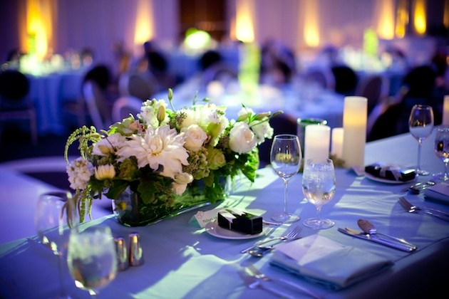 Blue reception lighting on table with white flower centerpiece