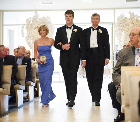 Groom walks down aisle with mom and dad in church