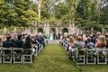 Atlanta History Center wedding ceremony on grass lawn stone walls greenery green garlands on chairs