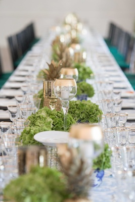 table runner, low candle holders, green flowers gold pineapple