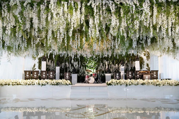 Greenery and white flower installation over white dance floor gold monogram live band stage white