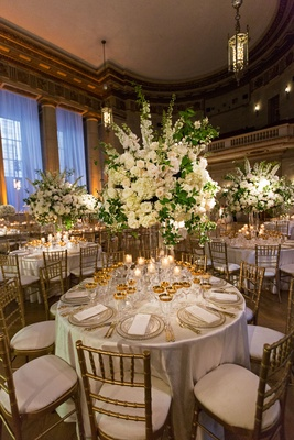 Wedding reception round table gold chairs gold glassware tall centerpiece white flowers greenery