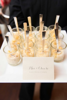 Glass cups of macaroni and cheese with duck confit mini spoons forks wedding appetizer