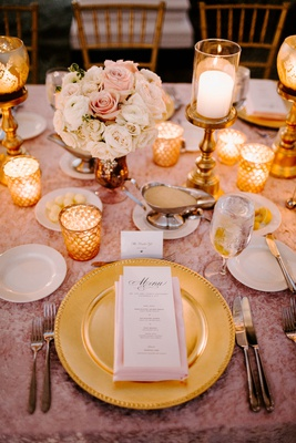 wedding reception tablescape place setting gold charger plate pink tablecloth gold candle low flower