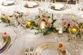 a long floral table runner with white pink and orange flowers next to gold charger plates