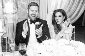 Black white photo bride in Inbal Dror wedding dress and groom in tuxedo clapping wedding speeches