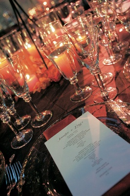Reception place setting with glass tableware and candles