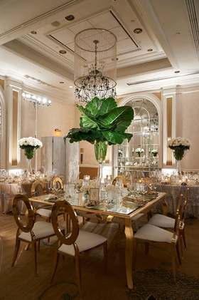 Wedding reception tall centerpiece banana leaves in vase with white roses at base gold chairs table