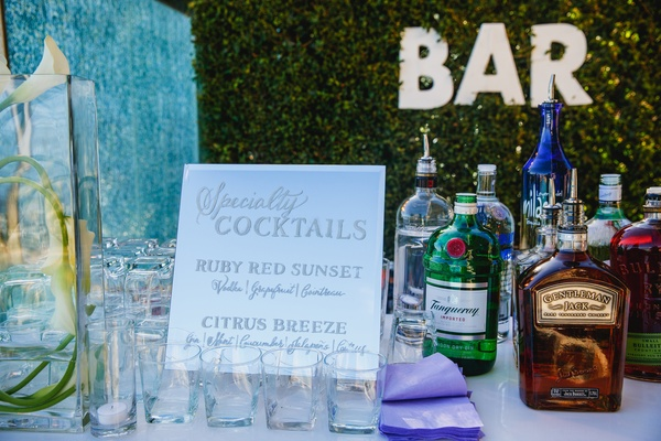 Specialty cocktail drinks featured at drinking station with BAR marquee letter sign
