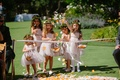 flower girls in blush dresses and greenery flower crowns throw petals outside aisle