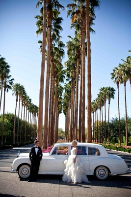 Newlyweds next to antique automobile and palm trees
