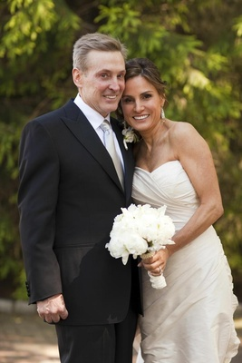 Bride in a strapless Romona Keveza gown and white bouquet with groom in a black tuxedo