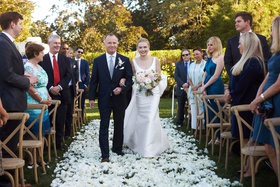 bride in classic wedding dress with pink dahlia bouquet father of bride white flowers on grass