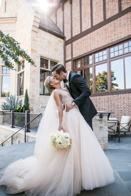Couple kisses after ceremony Monique Lhuillier dress