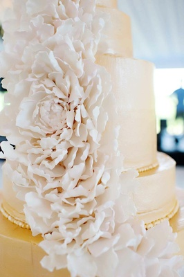 White peony flowers cascading down wedding cake