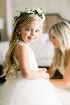 flower girl in white ball gown with lace straps long blonde hair flower crown greenery white roses