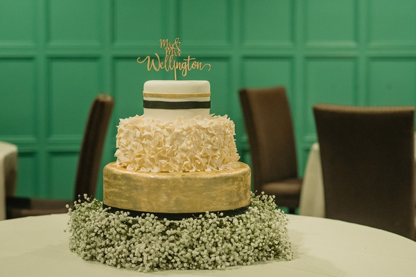 three tier wedding cake, gold layer, stripe layer, ruffled layer base on baby's breath