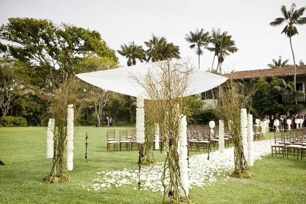 Grass lawn wedding ceremony surrounded by palm trees
