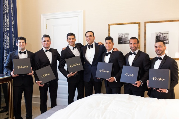 Groom and groomsmen in tuxedos bow ties holding boxes personalized with their names on them in gold