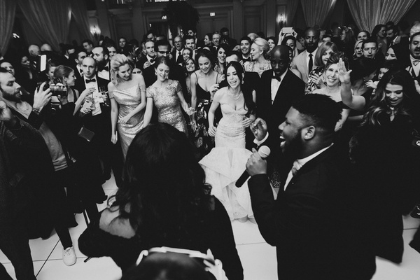black and white photo of live band singing and performing at wedding reception guests on dance floor