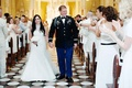 Bride and groom wedding recessional with guests in all white