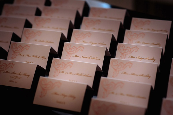 Pink design on escort card with gold script names and table numbers