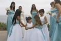 flower girls in white dresses hold hands in circle surrounded by bridesmaids in blue dresses