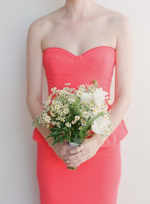 Coral bridesmaid holding daisy and greenery bouquet
