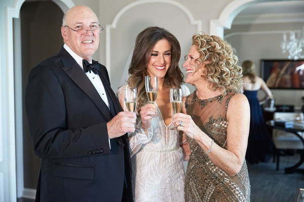 Bride in Inbal Dror wedding dress with mother and father tuxedo gold gown champagne flutes cheers