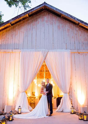 wedding reception in rustic chic barn bride in flower crown lanterns leading to reception space