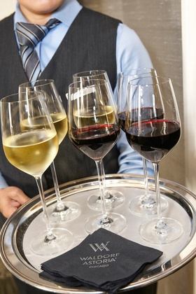 waldorf astoria chicago, server with a tray of wine glasses white and red glasses