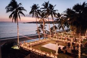 Destination wedding reception overlooking beach ocean palm trees dance floor u shaped table long